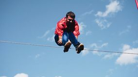 Cool tricks on the rope stretched above the ground. Close up. Performed by a man. stock footage