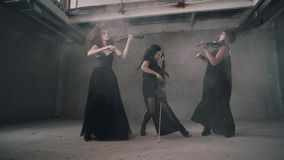 Cool trio of women violinists playing in a smoky room. Great performance. All the girls are dressed in black stock video footage