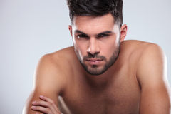 Cool undressed man sitting with hands crossed royalty free stock photography