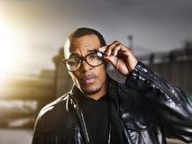 Cool urban african american man wearing glasses. Cool urban african american man  wearing glasses posing in urban setting Royalty Free Stock Photo