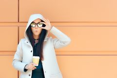 Cool Urban Fashion Girl With Hooded Coat and Coffee. Young woman with disposable paper cup drinking morning beverage Stock Images