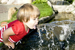 Cool water. Little and active girl tries to drink from a water fountain Stock Photos
