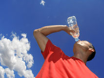 Cool water. Man drinking water against blue sky stock image
