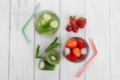 Cool water in glass, fresh green kiwi, mint and cucumber, strawberries and cherries. Fresh homemade vitamins royalty free stock photo