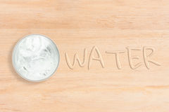 Cool water in glass with text. Cool water in glass place at left side wood texture background, WATER text water effect at right side of image Royalty Free Stock Images