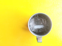 Cool. Water and ice in a cup made of stainless steel on yellow background and take from top view, space for text or copy Stock Images