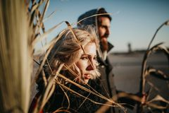 Blonde woman and her boyfriend posing at sunset while holding palm tree branches. Cool and weird young couple posing outdoors while holding palm tree branches stock image