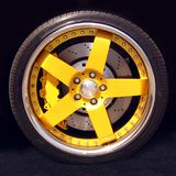 Sport car wheel. Detail of a modern yellow car wheel with tire and spokes Royalty Free Stock Photo