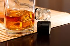 Cool whiskey. A glass of whiskey with ice and a bottle in the dark lacquered table Stock Images