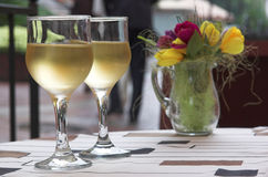 Cool white wine for a supper. White wine and vase with the flowers on a table Royalty Free Stock Photography