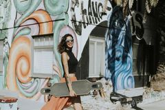 Cool woman with a longboard stock image