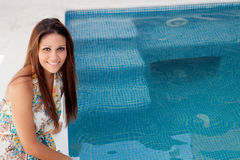 Cool woman sitting on the edge of the pool Royalty Free Stock Image
