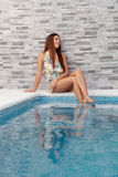 Cool woman sitting on the edge of the pool Royalty Free Stock Photo