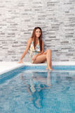 Cool woman sitting on the edge of the pool Stock Photography