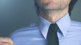 Cool young adult businessman adjusting his necktie stock footage
