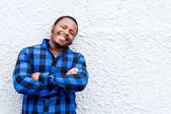 Cool young african man smiling against white wall Royalty Free Stock Photo