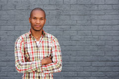 Cool young african man standing by gray wall with arms crossed Royalty Free Stock Image