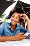 Cool young african woman smiling and holding cell phone. Portrait of a cool young african woman smiling and holding cell phone Stock Images