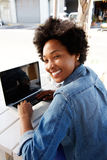 Cool young african woman working on laptop at outdoor cafe Stock Photo
