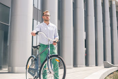 Cool young bearded hipster with bicycle on the city street. Smiling casual businessman having a break. He is standing in front of the building next to bike and Royalty Free Stock Images