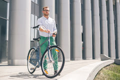 Cool young bearded hipster with bicycle on the city street. Smiling casual businessman having a break. He is standing in front of the building next to bike and Royalty Free Stock Photo
