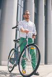 Cool young bearded hipster with bicycle on the city street. Smiling casual businessman having a break. He is standing in front of the building next to bike and Stock Image