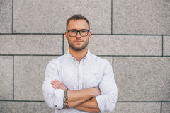 Cool young bearded hipster man wearing shirt, keeping arms crossed. And looking at camera while standing against concrete wall background Royalty Free Stock Image