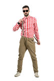 Cool young bearded hipster putting on suspenders. Royalty Free Stock Photography