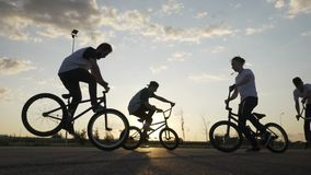 Cool young bikers team doing freestyle front wheelie trick outside with sunset in background -. Cool young bikers team doing freestyle front wheelie trick stock footage