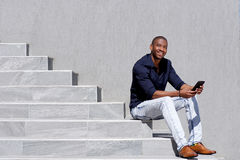 Cool young black guy sitting on steps using digital tablet Royalty Free Stock Images