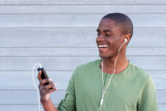 Cool young black guy smiling with MP3 player and earphones Royalty Free Stock Photos