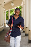 Cool young black guy walking outside with mobile phone and bag. Portrait of cool young black guy walking outside with mobile phone and bag Stock Photos