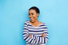 Cool young black woman laughing against blue wall Royalty Free Stock Photo
