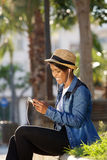 Cool young black woman listening to music with earphones Royalty Free Stock Image