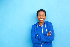 Cool young black woman smiling against blue background Royalty Free Stock Image