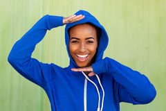 Cool young black woman smiling with hands raised Stock Photography