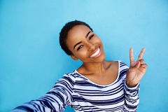 Cool young black woman taking selfie with peace hand sign Stock Photo