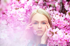 Cool young blonde with pink flower in mouth Royalty Free Stock Photos