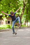 Cool young boy in Ollie position in the park royalty free stock image