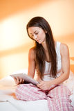 Cool young brunette using tablet. Royalty Free Stock Images