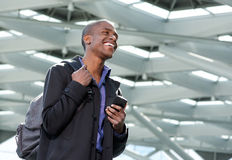 Cool young businessman walking with bag and cellphone Royalty Free Stock Photos