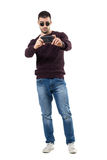 Cool young casual man recording video with mobile phone aiming at camera. Full body length portrait isolated over white studio background stock photography