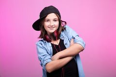 Cool young girl with headphones and hat. On pink background in studio photo Royalty Free Stock Image