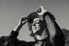 Cool young girl laughing outdoors in nature. Black and white. Black and white close up portrait of cute young woman with sunglasses touching her hat while Stock Images