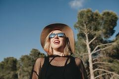 Cool young girl laughing outdoors in nature. Blonde charming blonde woman with sunglasses and hat enjoying nature with blue sky background Stock Photography
