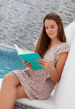 Cool young girl reading a book sitting on the edge of the pool Stock Images