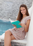 Cool young girl reading a book sitting on the edge of the pool Stock Photo