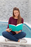 Cool young girl reading a book sitting on the edge of the pool Stock Photography