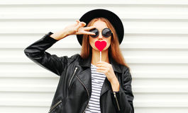 Cool young girl with red lollipop heart wearing fashion black hat leather jacket over white urban. Background Royalty Free Stock Photos