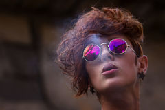 Cool young girl smoking tobacco. Fashionable teenage hipster girl with lip ring piercing and spiked trendy accessories posing Royalty Free Stock Images